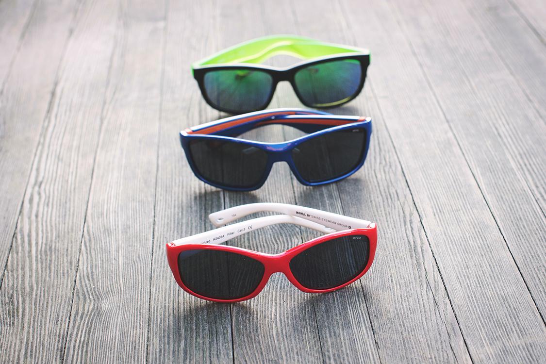 Bilde av tre par barnesolbriller fra Alliance Optikk: Invu rød solbrille til kr 295,-, Invu blå solbrille til kr 395,- og Mexx sorte og grønne til kr 495,-