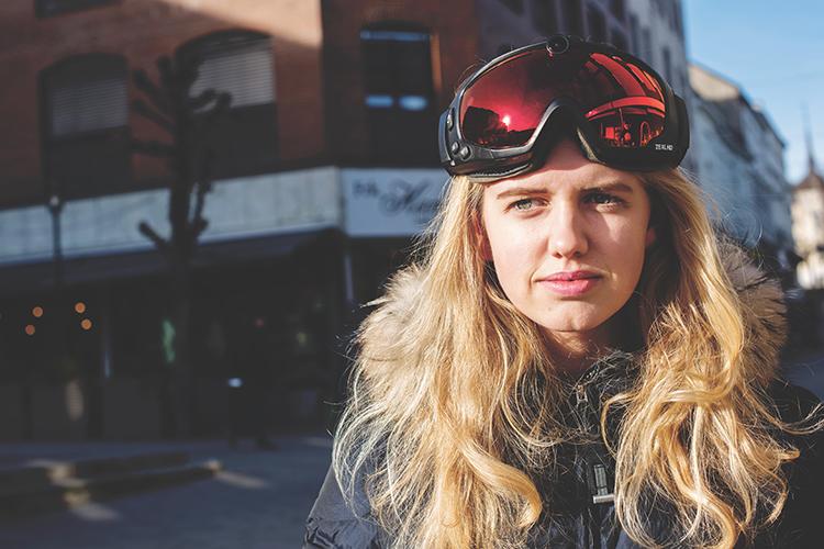 Bilde av en jente som viser frem Zeal googles med innebygd kamera i brillen fra Alliance Optikk